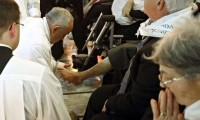 Pope Francis kneels to wash the foot of a man in a pre-Easter ritual