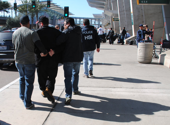 Joel A.Wright, second from left, was arrested at the San Diego airport on Friday. Credit U.S. Immigration and Customs Enforcement, via Associated Press